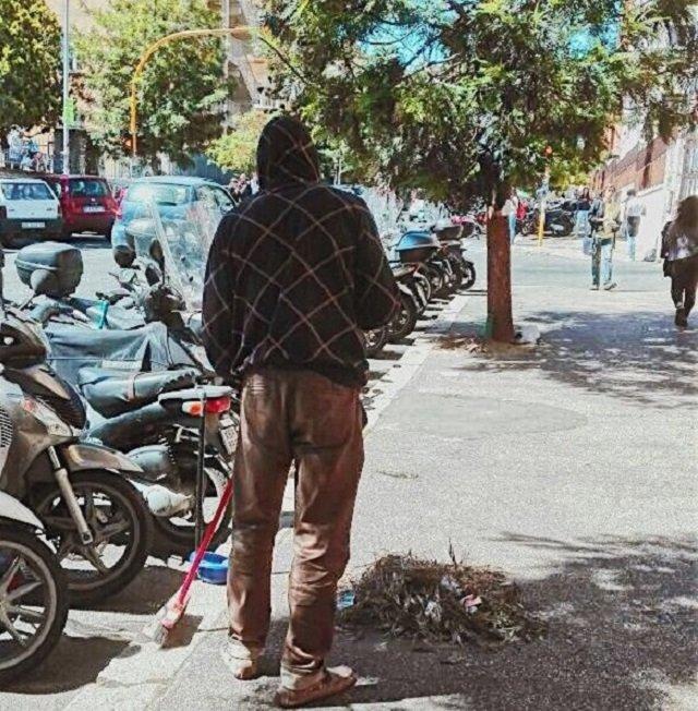 un ragazzo di colore fotografato di spalle che pullisce un marciapiede nei pressi della Sapienza a Roma