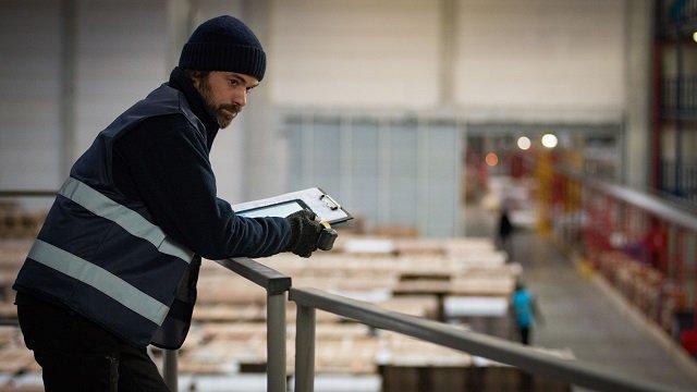 Romain Duris è in fabbrica affacciato da una balconata interna con sotto la produzione
